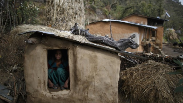 Uttara Saud sits inside a Chaupadi shed in the hills of Legudsen village in Achham District in western Nepal