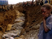 File photo of a Rwandan refugee girl staring at a mass grave