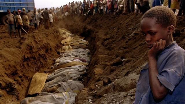 File photo of a Rwandan refugee girl staring at a mass grave