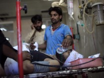 Medics attend to a man, injured in a bomb blast at a vegetable market, at PIMS in Islamabad