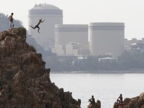 File photo of a man on vacation diving into the sea as Kansai Electric Power Co.'s Mihama nuclear power plant is seen in the background in Mihama town, Fukui prefecture