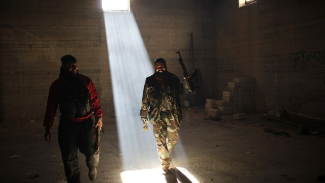 A Free Syrian Army fighter smiles in a bunker they use to take shelter from fighter jet air-strikes in Aleppo
