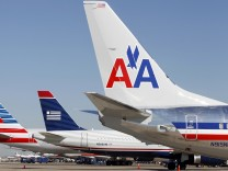 The tail sections of a newly designed American Airlines aircraft,  a US Airways aircraft and a traditional American Airlines aircraft are lined up at at Dallas-Ft Worth International Airport in this file photo