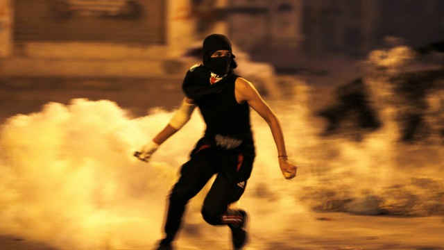 Anti-government protester runs holding teargas canister fired by riot police during clashes after procession to visit grave of Abdulsamad in Salmabad