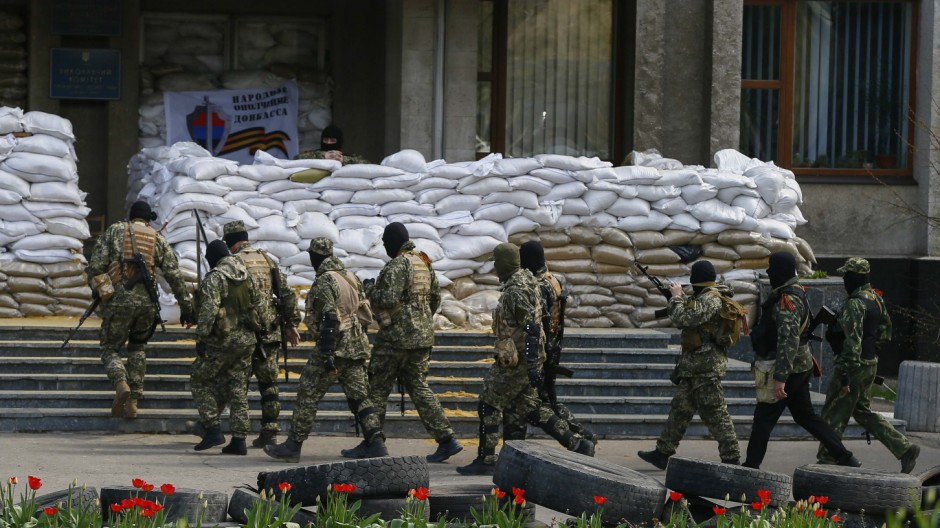Armed men pass by barricades outside the mayor's office in Slaviansk