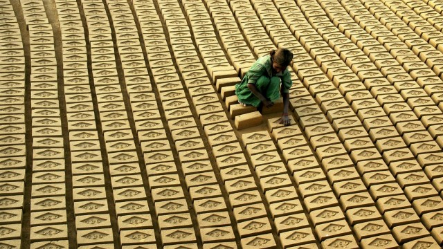 Indian child labourer arranges bricks at a brick factory in Tharvai village