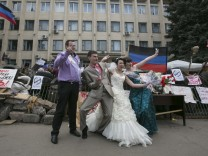 People pose in front of barricades outside a regional government building seized by pro-Russian armed men in Kramatorsk