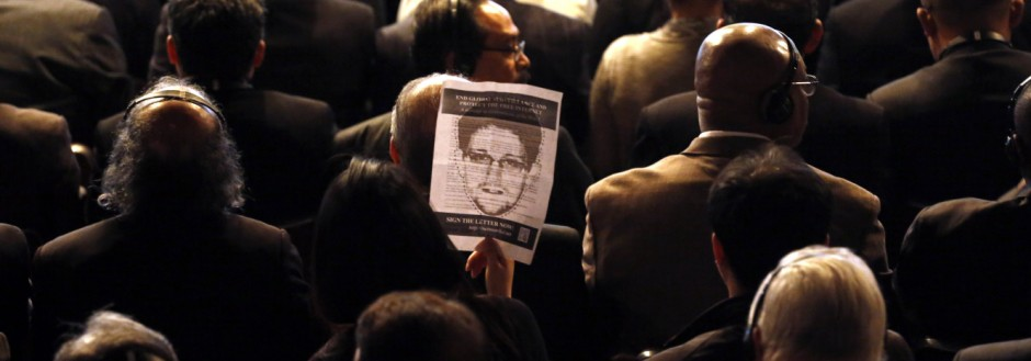 An attendee holds a sign showing Edward Snowden during the NETmundial: Global Multistakeholder Meeting on the Future of Internet Governance in Sao Paulo