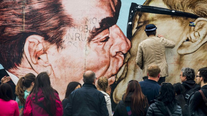 Artist Dimitry Vrubel cleans his mural 'Fraternal Kiss' at the East Side Gallery in Berlin