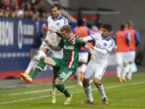 Augsburg's Hahn fights for the ball against Hamburger SV's Diekmeier and Arslan during their German first division Bundesliga soccer match in Augsburg