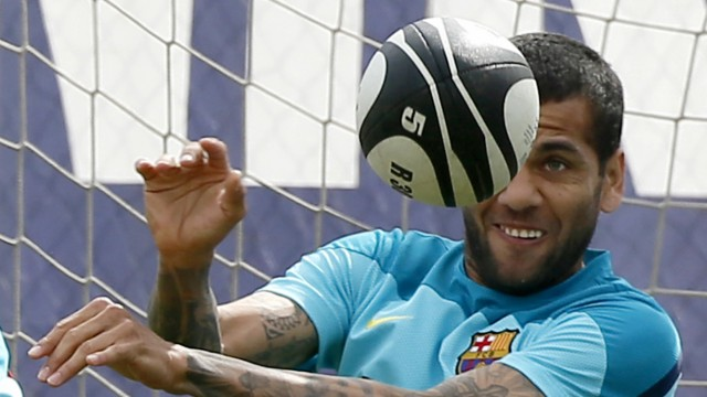 Barcelona's Dani Alves plays with a rugby ball during a training session near Barcelona