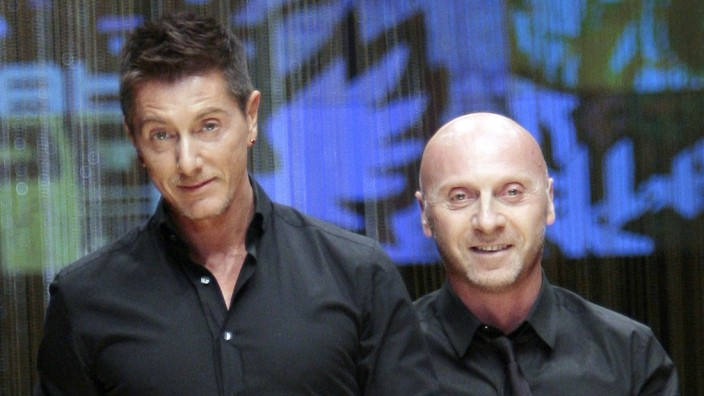 File photo of designers Dolce and Gabbana acknowledging the applause at the end of their D&G's Spring/Summer 2008 men's collection show in Milan