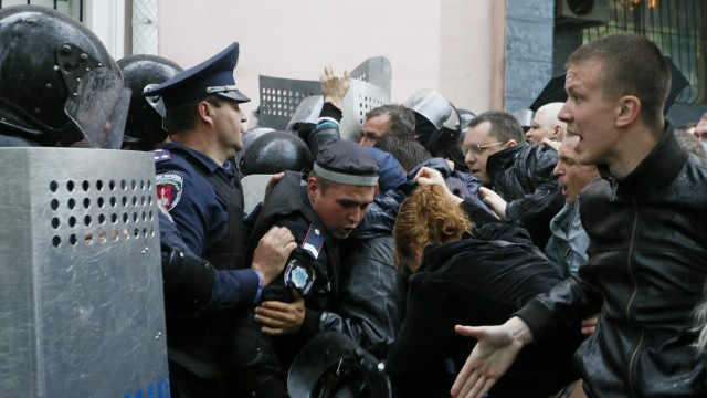 Ukrainian Interior Ministry security forces members block participants of a rally outside a city police department in Odessa