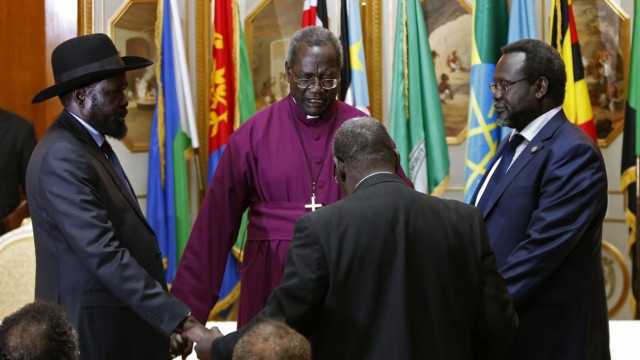 South Sudan's rebel leader Riek Machar and South Sudan's President Salva Kiir hold a priest's hands as they pray before signing a peace agreement in Addis Ababa
