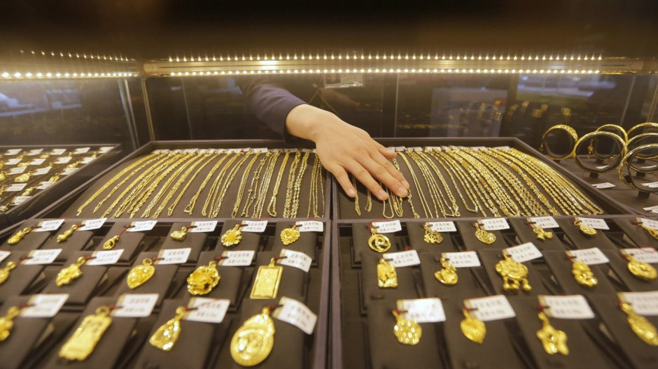 File photo of an employee arranging gold jewellery in the counter of a gold shop in Wuhan