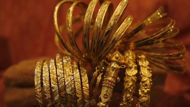 A jewellery shop owner counts gold bangles in Kolkata