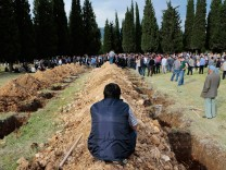 A man sits near graves during the funeral of a miner who died in a fire at a coal mine, in Soma