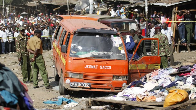 Policemen inspect a damaged public transport van wrecked at the scene of a twin explosion at the Gikomba open-air market for second hand clothes in Nairobi
