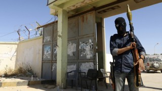 A militia stands guard in front of the entrance to the February 17 militia camp after Libyan irregular forces clashed with them in Benghazi