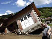 A man reacts near a house tilted by floods in the village of Krupanj