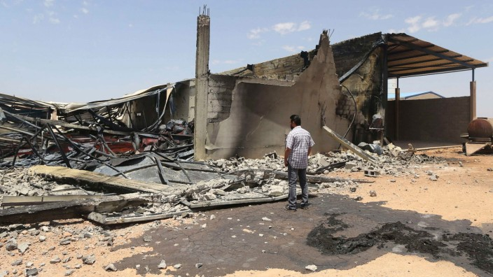 A man looks at destroyed warehouses following Friday's clashes between Libyan irregular forces and Islamist militias in Benghazi