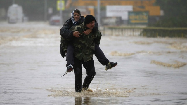 A man carries a woman through a flooded street in the town of Obrenovac, east from Belgrade