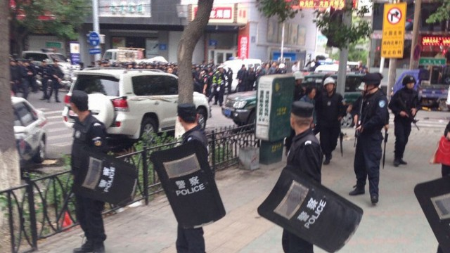 Riot policemen look behind them toward the site of an explosion, which has been cordoned off, as they stand guard in downtown Urumqi