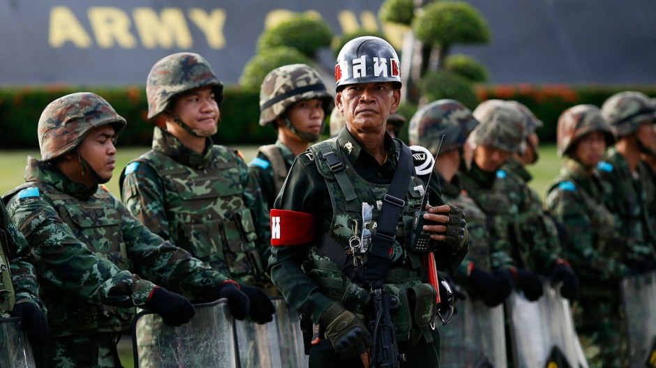 A Thai officer holds a weapon as his unit blocks the access to the Army Club where Thailand's army chief held a meeting with all rival factions during a coup in central Bangkok