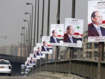 A car travels past posters of presidential candidate and Egypt's former army chief and Abdel Fattah al-Sisi on a bridge in Cairo