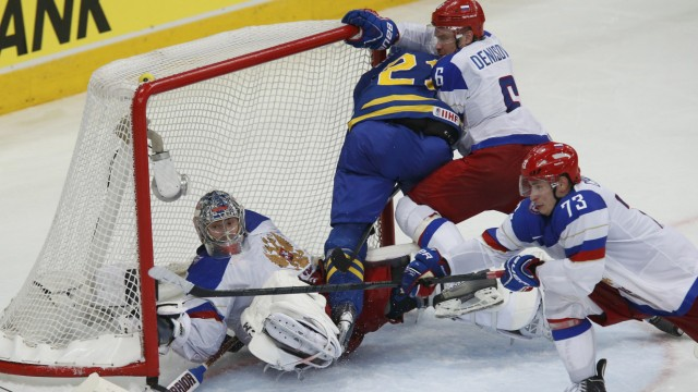 Russia's goalie Bobrovski saves as team mate Denisov checks Sweden's Ericsson into the net during their men's ice hockey World Championship semi-final game at Minsk Arena in Minsk