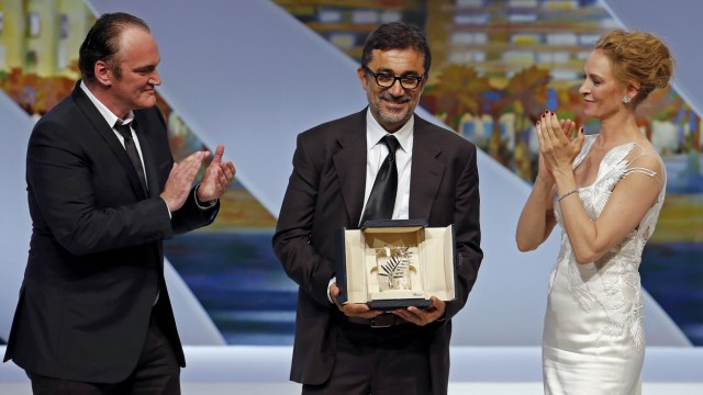 Director Nuri Bilge Ceylan, Palme d'Or award winner for his film 'Winter Sleep', poses on stage next to director Quentin Tarantino and actress Uma Thurman during the closing ceremony of the 67th Cannes Film Festival in Cannes