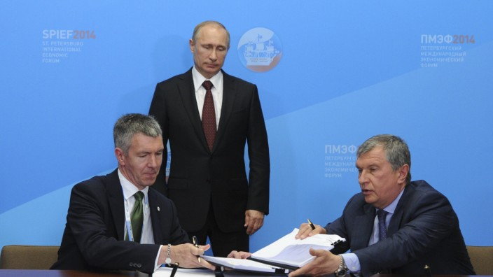 Rosneft President Sechin and BP Russia head Campbell sign documents as Russia's President Putin stands nearby during a signing ceremony at the St. Petersburg International Economic Forum 2014 in St. Petersburg
