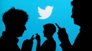 File illustration photo of people holding mobile phones silhouetted against a backdrop projected with the Twitter logo  in Warsaw