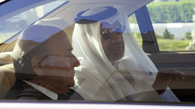 Mohamed Bin Hammam, the president of the AFC, talks with FIFA President Blatter as they leave Doha airport