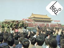 Chinese marchers are jubilant as they surround and stop an army truck at...