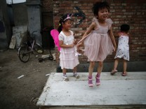 Children play on abandoned wood panels in Dongxiaokou village in Beijing
