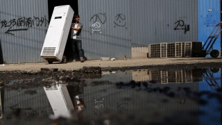 A recycling worker moves an air-conditioning unit in Dongxiaokou village in Beijing