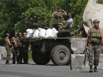 Ukrainian servicemen stand guard at a checkpoint near the town of Amvrosievka, in Donetsk region