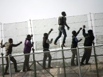 African migrants climb a border fence covered in razor wire between Morocco and Spain's north African enclave of Melilla