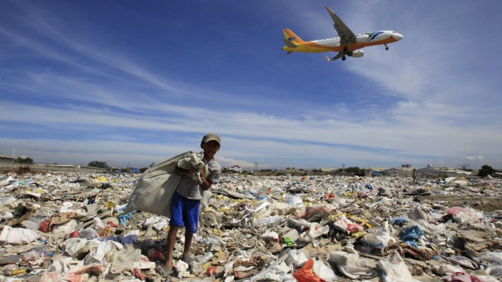 An aircraft flies overhead as a person rummages for recyclables at a garbage dumpsite in Paranaque city