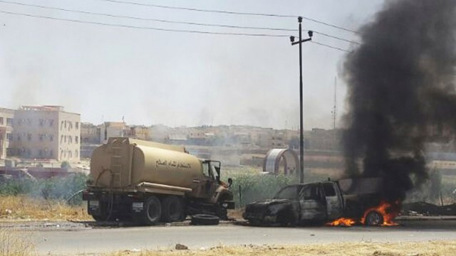 Burning vehicles belonging to Iraqi security forces are seen during clashes between Iraqi security forces and al Qaeda-linked ISIL in Mosul
