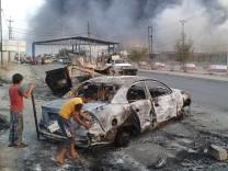 Irakische Kinder untersuchen ein Autowrack - im Hintergrund stehen Rauchwolken über der eingenommenen Stadt Mosul