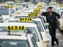 A taxi driver listens to speeches by his colleagues, during an Europe-wide protest of licensed taxi drivers against taxi hailing apps that are feared to flush unregulated private drivers into the market, in Berlin