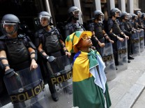 A young soccer fan stands in front of a police line during the fifth day of metro worker's protest in Sao Paulo