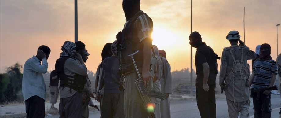Fighters of the Islamic State of Iraq and the Levant (ISIL) stand guard at a checkpoint in the northern Iraq city of Mosul