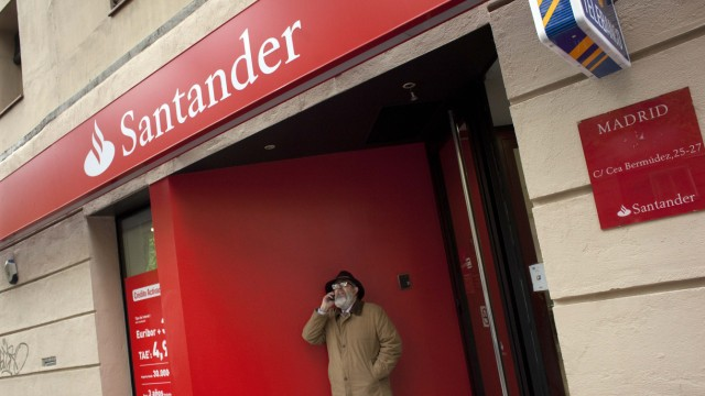 A man talks on his cell phone as he walks out from a branch of Spanish largest bank Santander in Madrid