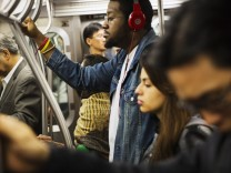 A commuter listens to Beats brand headphones while riding subway in New York