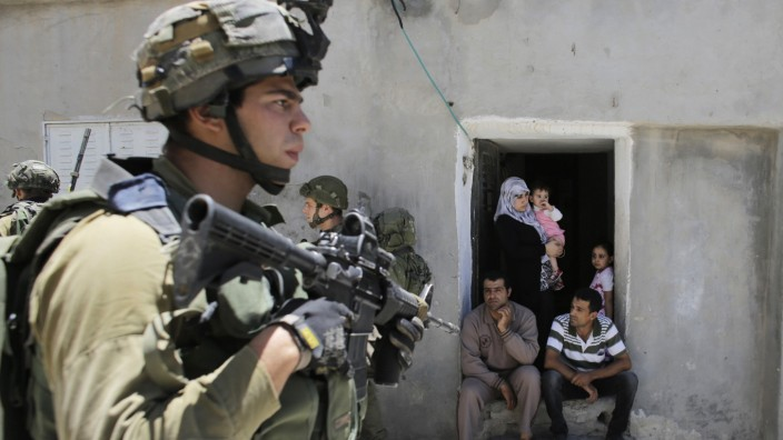 Palestinians sit outside their house as Israeli soldiers patrol near Hebron