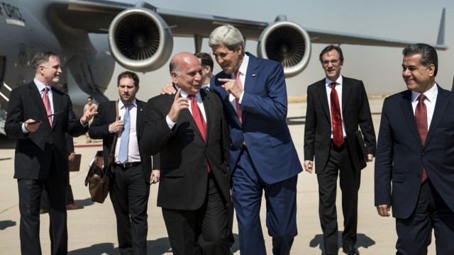 U.S. Secretary of State Kerry talks with Hussein, chief of staff at the presidency of the Kurdistan Regional Government, while accompanied by Kurdish regional foreign relations minister Bakir and other officials, at Arbil International Airport