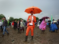 A man dressed in an orange suit watches Robert Plant on the Pyramid stage at Worthy Farm in Somerset, during the Glastonbury Festival